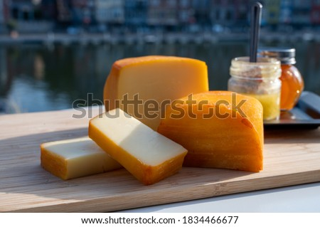 Photo of  Cheese collection, tasty Belgian abbey cheeses made with brown trappist beer and fine herbs and view on Maas river in Dinant, Wallonia, Belgium