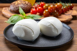 Cheese collection, white balls of soft Italian cheese mozzarella, served with red cherry tomatoes, fresh basil leaves close up