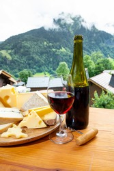 Cheese collection, wooden board with French cheeses comte, beaufort, abondance, emmental, morbier, red wine from Savoie and french mountains village in Haute-Savoie in summer on background