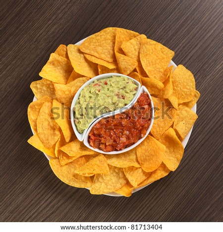Cheese flavored nachos with guacamole (sauce based on avocado) and tomato salsa