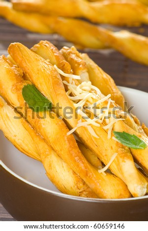 Cheese flavored salty twisted sticks on table cover with mint leaves.