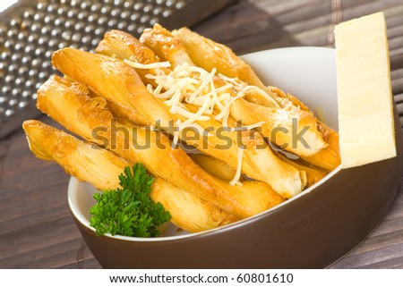 Cheese flavored salty twisted sticks on table cover with parsley.