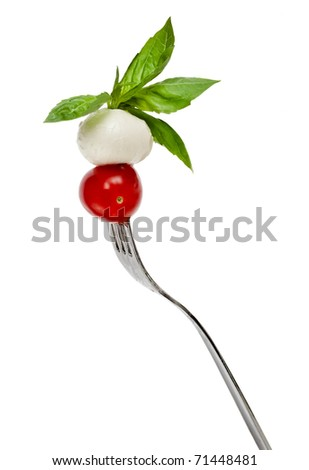 cheese mozzarella, basil and tomatoes  on a fork isolated on white background