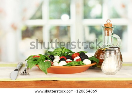 cheese mozzarella with vegetables in the plate with fork and knife on wooden table