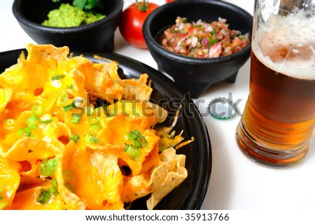 Cheese nachos with sides of guacamole and salsa with an ice cold bottled beer poured in a glass - stock photo