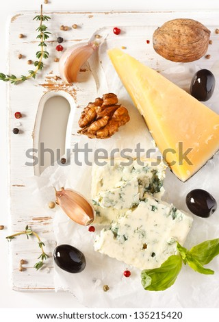 Cheese, olives and walnuts on an old white cutting board. - stock photo