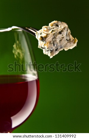 Cheese on a fork and glass with red wine