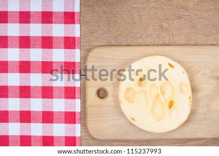Cheese on board, tablecloth and wooden texture background
