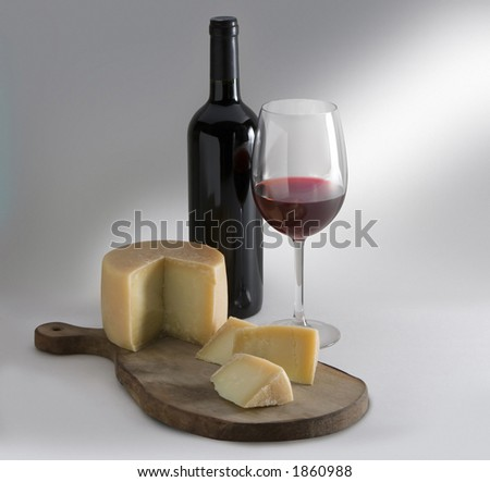 Cheese on board with wine cup and bottle