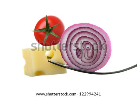 cheese onion and tomato on forks against white background