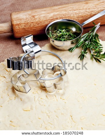 Cheese pastry dough with rolling pin on dark background