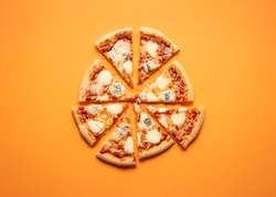 Cheese pizza cut in equal pieces on an orange seamless background. Flat lay of four cheese pizza. Quattro formaggi Italian pizza.