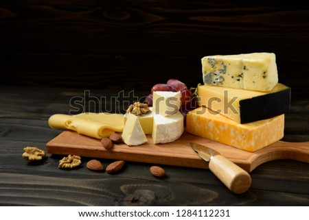 Cheese plate: Parmesan, cheddar, gouda, camembert, brie,  and other with nuts on wooden board on dark background with place for text. Tasty appetizers.  Copy space.