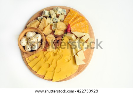 Cheese plate: Parmesan, cheddar, gouda, mozzarella and other with chili pepper and almonds on wooden board. Tasty appetizers. Isolated. Top view.