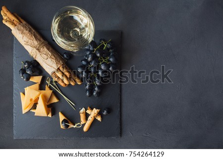 Cheese plate served with crackers, grapes and glass of white wine on dark background. Old gouda cheese on tasting plate. Top view with space for text. ストックフォト ©