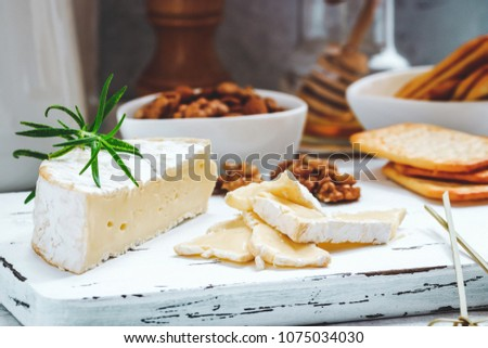 Cheese plate served with crackers, honey and nuts. Camembert on white wood serving board over white texture background. Appetizer theme. #1075034030