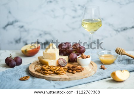 Cheese plate served with grapes, honey, crackers and nuts on a wooden plate