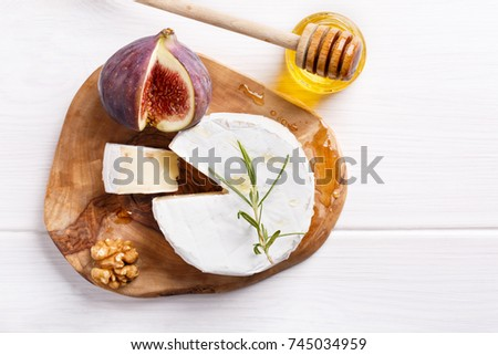 Cheese plate with brie, figs, honey and nuts on white table. Top view. Copy space.