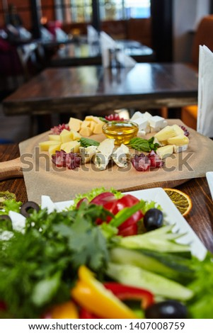 Cheese platter in focus image. Appetizer presentation with food decorations. Blurry background, blurry greenery platter forground