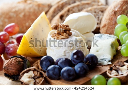 Cheese platter: variety of cheeses on wooden plate with fruits and bread