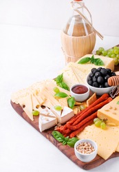 Cheese platter with assorted cheese, sausage, jam, black olives, pine nuts and grapes. Appetizer variation and bottle of white wine