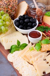 Cheese platter with assorted cheese, sausage, jam, black olives, pine nuts and grapes topped with basil. Appetizer variation