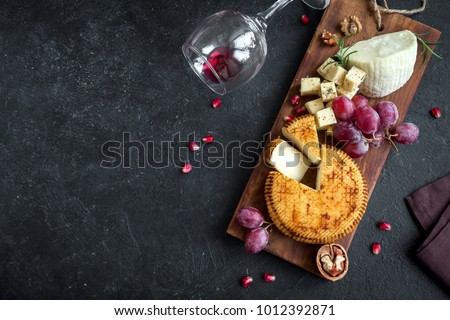 Cheese platter with assorted cheeses, grapes, nuts over black background, copy space. Italian cheese and fruit platter with honey and wine.
