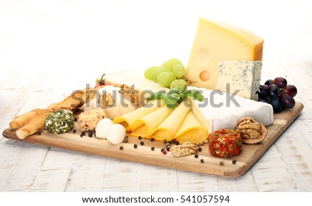 Cheese platter with different cheese and grapes - some emmental, gauda, parmesan and brie cheese on a table for brunch