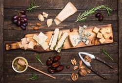 Cheese platter with different cheeses, grapes, nuts, honey, bread and dates on rustic wooden background. Retro styled cheese variety selection on dark wood board.