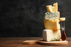 Cheese platter: yellow Maasdam, white Camembert and blue cheese Dor Blue with rosemary and fork on wooden cutting board on black background. Copy space.  Concept serving cheese.