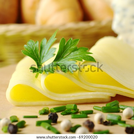 Cheese slices and parsley with chives and pepper corns in the front and bread basket in the back (Selective Focus, Focus on the front of the cheese slices and the parsley)