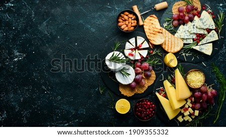 Cheese. Slices of cheese on plates: brie, blue, gorgonzola, parmesan and maasdam on a black stone background. Free copy space. Top view.