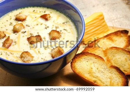 Cheese soup with toasts in blue pottery