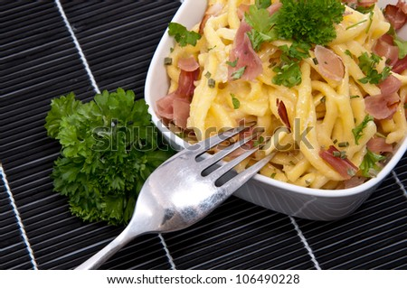 Cheese Spaetzle in a Bowl decorated with Parsley and cutlery on a black tablecloth