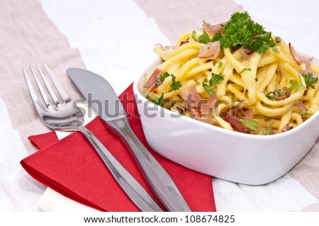 Cheese Spaetzle with fresh herbs on red striped tablecloth