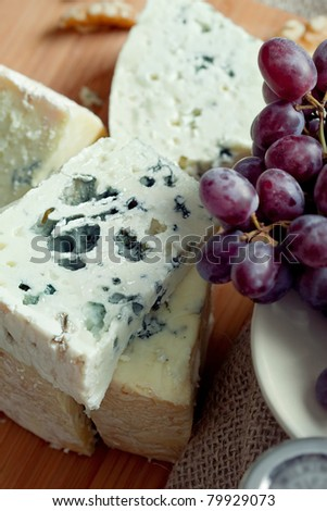 Cheese still life with red grapes and walnuts