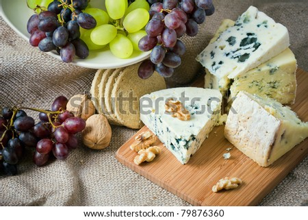 Cheese still life with red grapes, walnuts and crackers - stock photo