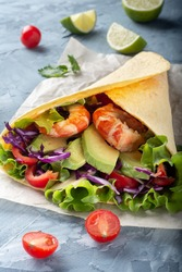 Cheese tortilla with avocado and vegetables. Tortilla with vegetables and shrimp. Tortilla from the sea.