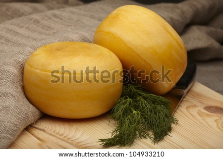 cheese wheels with dill on wooden table
