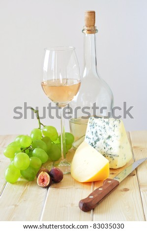 Cheese, white wine, grapes and figs on a wooden table