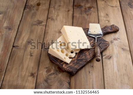 Cheese with holes is cut into portions on a wooden board, a useful dairy product. Tasty food. Country style photo. Place for text. Copy space,