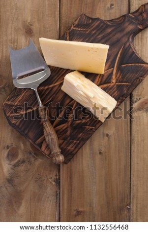 Cheese with holes is cut into portions on a wooden board, a useful dairy product. Tasty food. Country style photo. Place for text. Copy space.