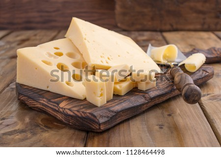 Cheese with holes large and small. Wooden board and knife. Traditional Dutch cheese. Copy space
