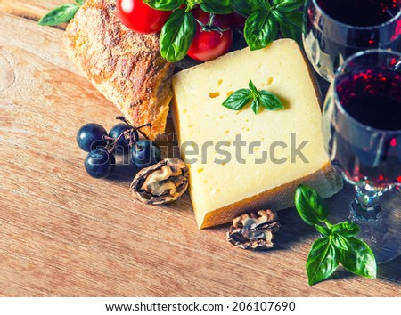 cheese with red wine and walnuts. food and beverages. retro style toned picture. selective focus