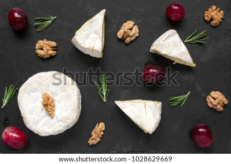Cheese with white mold. composition of camembert or brie cheese with grapes, walnuts and of rosemary. top view. Healthy breakfast