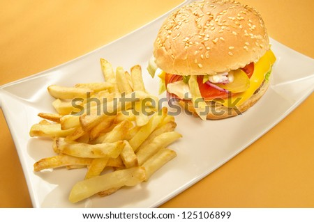 Cheeseburger and chips on a plate, yellow background