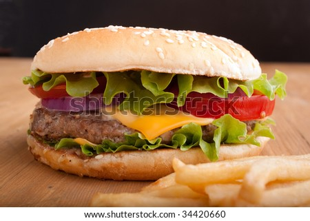 cheeseburger and french fries on a wooden table on black background