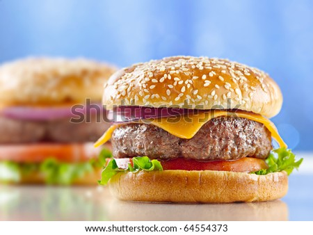 cheeseburger with blue background and selective focus