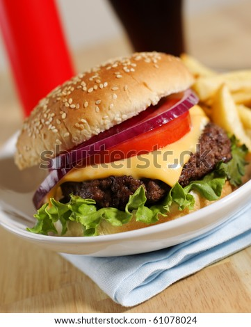 cheeseburger with french fries on a white plate with cola drink and ketchup in the background. Shallow depth of field.