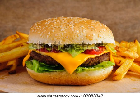 Cheeseburger with french fries on a wooden plate